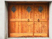 Porte de garage à deux portes avec fenêtres extérieures à l'extérieur recouvertes de bois
